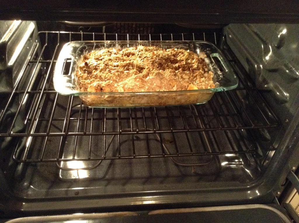 Picture of apple crisp in clear baking dish going into the oven