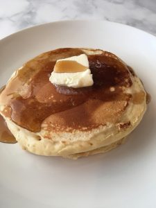 Photo of pancakes with butter and syrup.