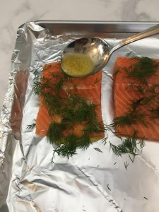 Photo of pouring butter sauce on salmon.