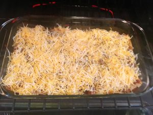 Photo of adding cheese to the enchiladas.