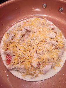 Photo of tortilla with chicken, veggies, and cheese.