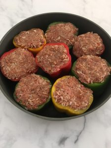 Photo of bell peppers stuffed with meat mixture.