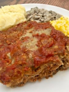 Photo of meatloaf served with a generous portion of mashed potatoes, mushroom gravy, and creamed corn.