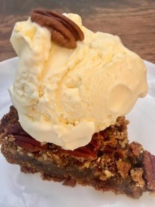 Photo of a slice of pecan pie with vanilla ice cream.