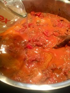 Photo of adding chicken stock to the bolognese meat sauce.