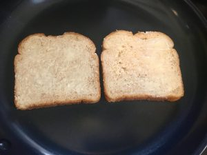 Photo of buttered bread in a pan.