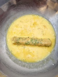 Photo of re-rolling mozzarella stick in egg mixture.