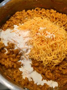 Photo of adding cheese and cream to meat sauce with pasta.