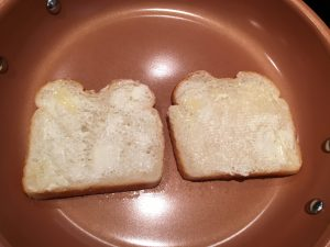 Buttered bread in a pan.