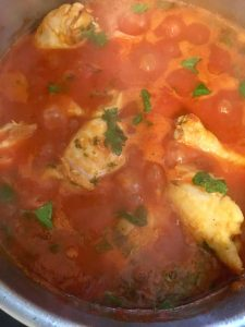 Chicken cooking in chicken stock and tomato sauce.
