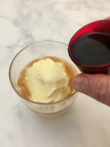 Pouring espresso over ice cream to make an affogato.