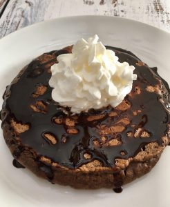 Chocolate Pancake with plenty of chocolate syrup and whipped cream.