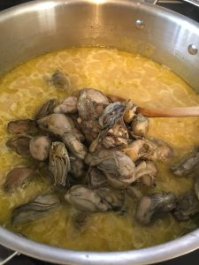 Whole canned oysters being added to the rice.